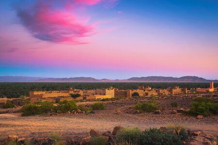 Sunset above a moroccan village with Atlas mountains in the background Standard-Bild - 127114947
