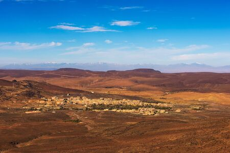 View over a village in Morocco with snowy Atlas mountains in the background Standard-Bild - 127114862