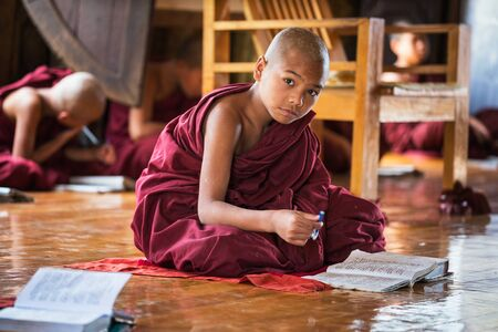 Asian child monk learning from his school book Sajtókép
