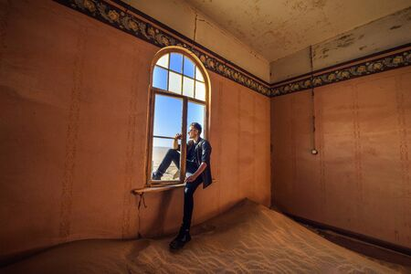 Tourist sits in the window of a room in the ghost town Kolmanskop, Namibia