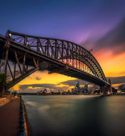 Sunset skyline of Sydney downtown with city lights and Harbour Bridge