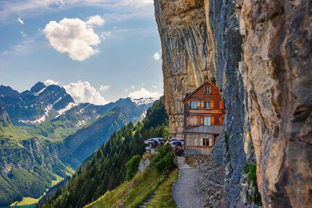 Swiss Alps and a restaurant under a cliff on mountain Ebenalp in Switzerland 스톡 콘텐츠