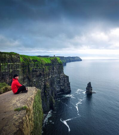 Hiker sitting at the cliffs of Moher 免版税图像