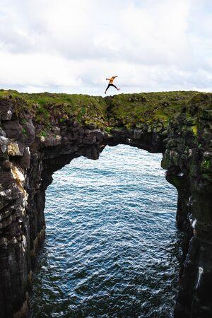 Tourist jumps over a natural rock bridge in Arnarstapi, Iceland Zdjęcie Seryjne