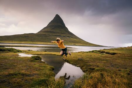 Young hiker jumps over a stream at the Kirkjufell mountain in Iceland