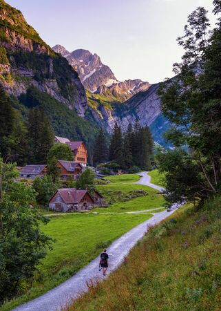 Tourist walks down the path to Seealpsee lake in the Swiss Alps