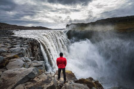 Hiker standing close to the Dettifoss waterfall in Iceland 版權商用圖片