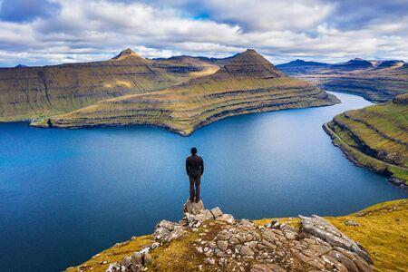 Hiker enjoys spectacular views over fjords from the summit of a mountain near Funningur on Faroe Islands. 版權商用圖片