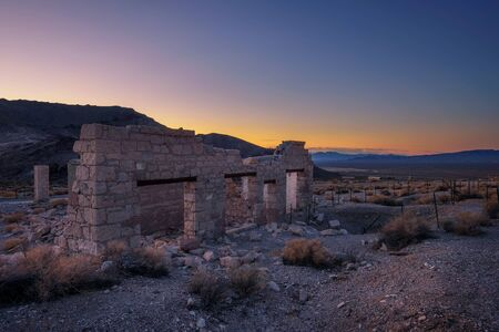 Sunrise above ruined building in the town of Rhyolite, Nevada. This ghost town is located in Nye County among Bullfrog Hills near Death Valley.