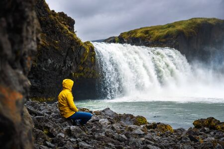 Tourist in a yellow jacket relaxing at the Godafoss waterfall in Iceland. Godafoss means the waterfall of the gods in icelandic. 免版税图像