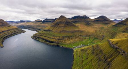 Aerial view of mountains and ocean around village of Funningur on Faroe Islands