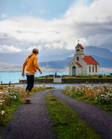 Young skater skateboarding towards a church and a cemetery in Iceland