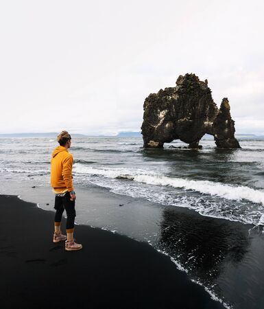Tourist looks at the Hvitserkur basalt stack in northern Iceland 스톡 콘텐츠
