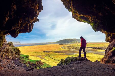 Hiker in the Loftsalahellir Cave near the village of Vik in Iceland 스톡 콘텐츠