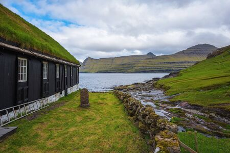 Small wooden village church with a tomb stone in Faroe Islands, Denmark