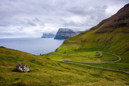Road going to the village of Trollanes located on the island of Kalsoy in Faroe Islands with mountains of Kunoy and Bordoy in the background.