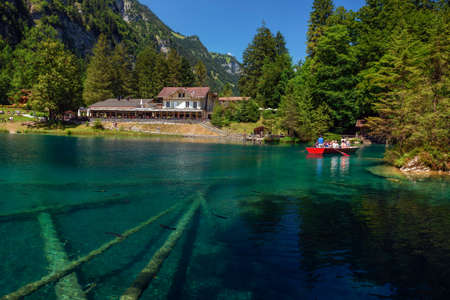 Tourists taking a boat trip on Blausee Lake in Switzerland