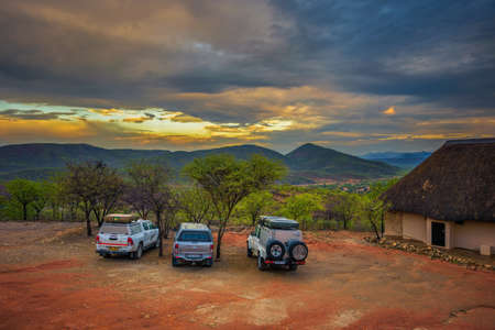 Suv cars parked at a tourist campsite in Namibia at sunset
