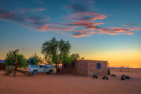 Sunset at a desert camp in Namibia with a pickup 4x4 car with a roof tent