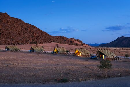 Evening at small chalets of a desert lodge near Sossusvlei in Namibia 스톡 콘텐츠