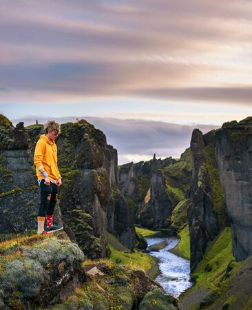 Young hiker standing at the edge of the Fjadrargljufur Canyon in Iceland