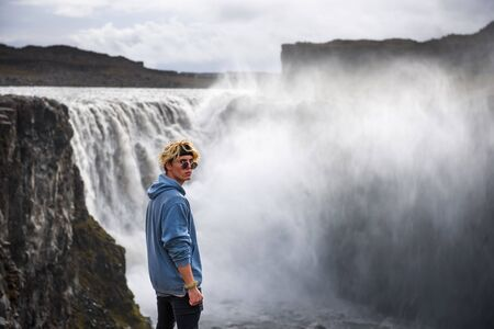 Hiker standing at the edge of the Dettifoss waterfall in Iceland 스톡 콘텐츠