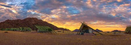 Sunrise above small chalets of a desert lodge near Sossusvlei in Namibia 스톡 콘텐츠