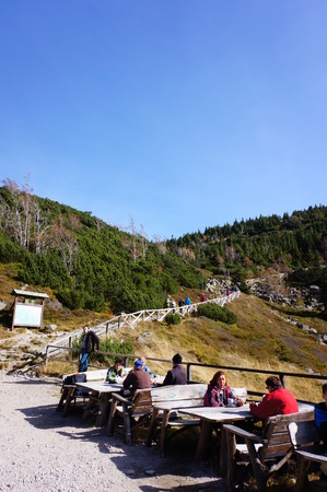People sitting around wooden tables by a mountain close to Karpacz in Poland