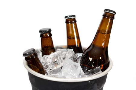 A black ice bucket with four brown glass bottles of beer on a white background.