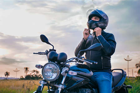 Man sitting on a motorcycle, wearing jeans and a black jacket, fastening his helmet with a landscape in the background.