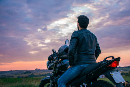 Man sitting on a black motorcycle, wearing blue jeans, a black jacket and a black helmet, with his back turned against a landscape in the background.