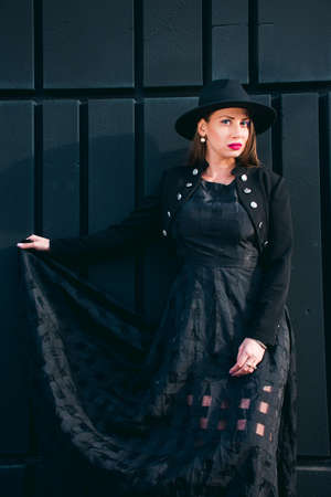 Fashion photography with a light skinned young woman with blonde hair dressed in a long black dress, black bullfighter and hat posing against a black wall.