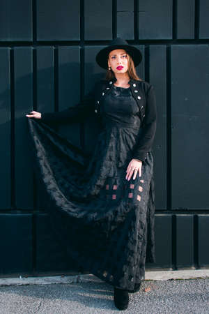 Fashion photo with a light skinned young woman with blonde hair dressed in a long black dress, black bullfighter and hat posing against a black wall.