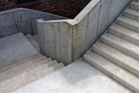 Three perpendicular flights of raw concrete stairs with two landings outside of a building.