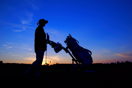 Golf, woman golfer with golf bag at sunset, as backgrounds photo