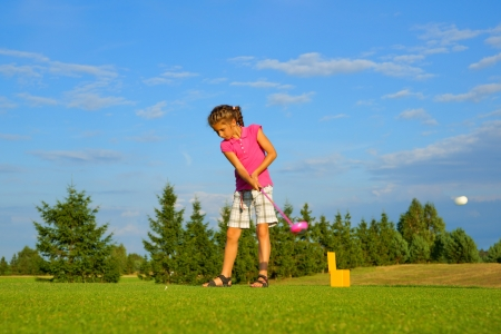 Golf, girl golfer hitting the ball photo
