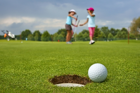 Golf, ball lying on the green next to hole, in the background of the two young golfers photo