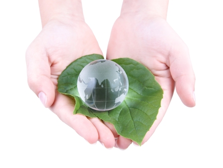 Glass Globe in the leaves and the child s hands, isolated on white background photo