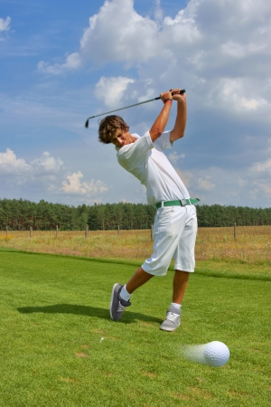 Golf, golfer striking the ball photo