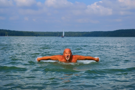 Swimmer, Senior man swimming butterfly strokes  Caucasian male aged 60 years photo