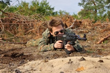 paramilitary: Teenager, boy lying in his battle dress, sunglasses and a rifle, Air Soft Gun