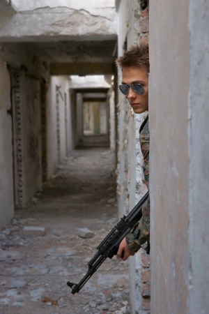Teenager, boy in battle dress and a rifle, Air Soft Gun photo