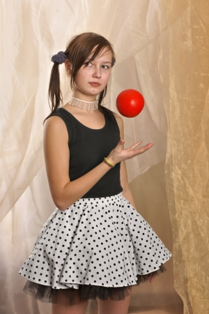 Teenager, girl in standing position, dressed in a T-shirt and mini skirt, tossing an apple photo