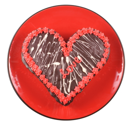 Chocolate cake in the shape of a heart with the word love on a red plate photo