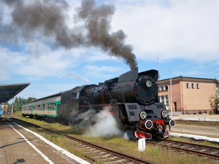 Railways, steam locomotive with wagon, train leaving the station photo