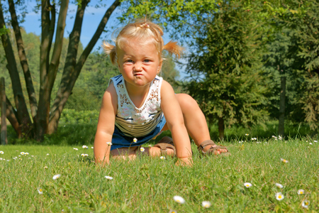 Child, little girl having fun on the meadow, with a grimace on his face photo