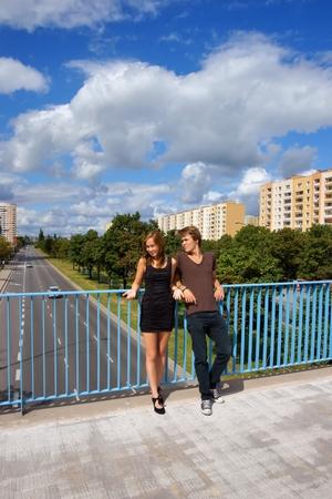 elevated walkway: Girl and boy, teens are standing based the balustrade elevated walkway