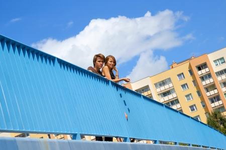 elevated walkway: Girl and boy, teens are standing behind the elevated walkway balustrade Stock Photo