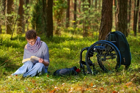Disabled woman reading a book in the forest, wheelchair photo