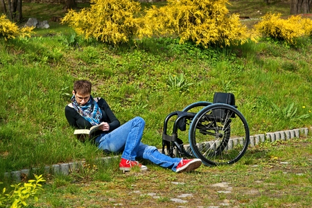 Disabled woman reading a book in the park, wheelchair